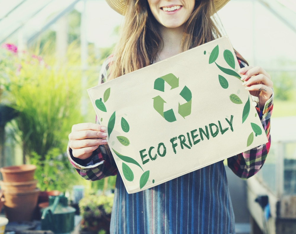 Woman holding Eco Friendly sign - image by Love Thyself
